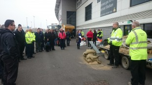 Our field team demonstrating how to build an effective sand bag wall