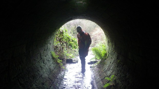 A member of the confined spaces team inspects a tunnel