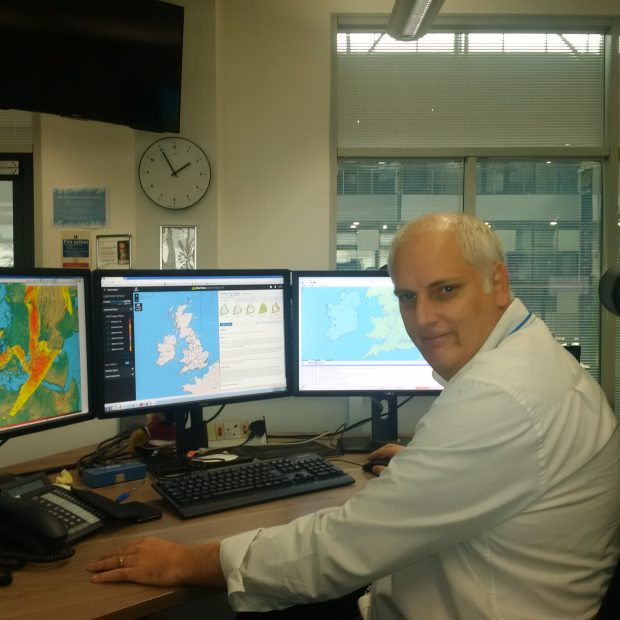 Brian Vinall sits at his desk in the flood forecasting centre