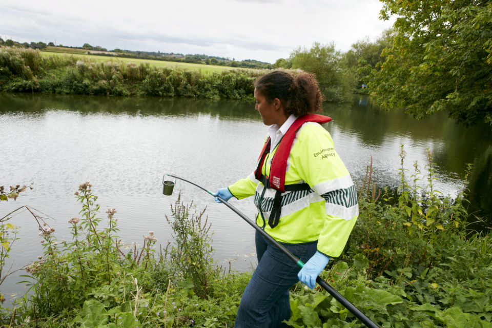 An Environment Officer samples a river for pollution