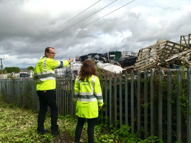 Environment Agency workers looking at illegal waste