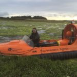 Cormac Meenehan in an orange hovercraft on the shore with water and weed in the background