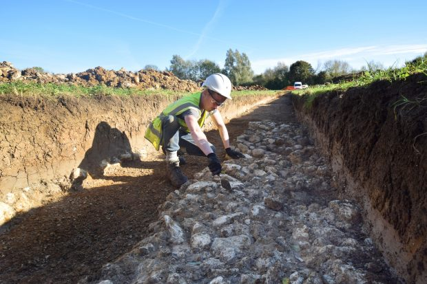 EA archaeologist working in a trench on a stone causeway
