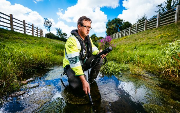 An environment agency officer crouching in a stream conducting water monitoring