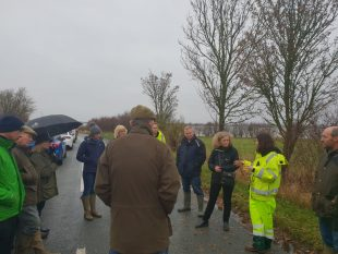 Emma Howard Boyd on a road talking to an Environment Agency officer involve din flood response and wearing hi-vis overalls with a group of people listening nearby