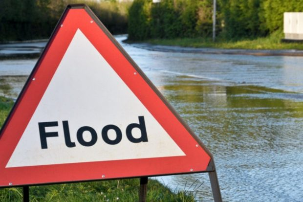 flood sign in front of flood water
