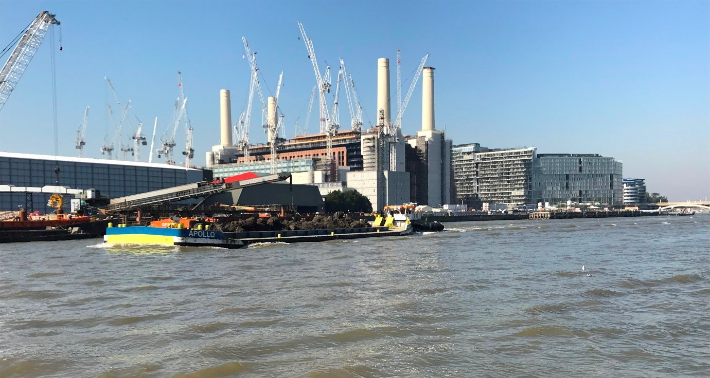 Former Battersea Power Station next to River Thames with river barge carrying spoil.