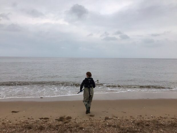 Ruth Sanderson on a beach sampling bathing water