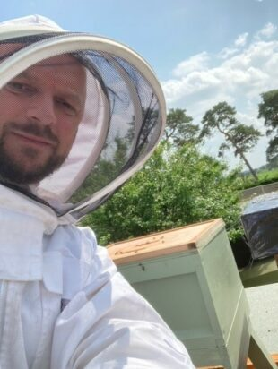 An Environment Agency officer in a bee keeping suit next to one of his bee hives.